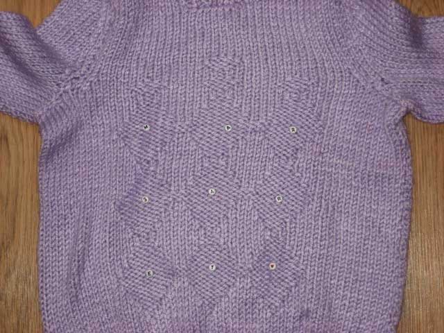Margaret's purple sweater with buttons across the midsection